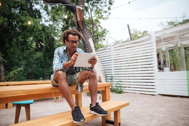 Knappe jonge man in glazen met tablet zitten in park