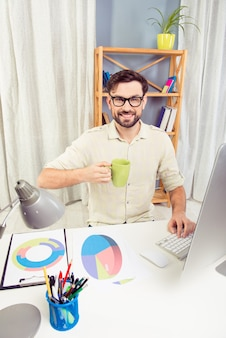 Knappe jonge man in glazen werken in kantoor en het drinken van thee