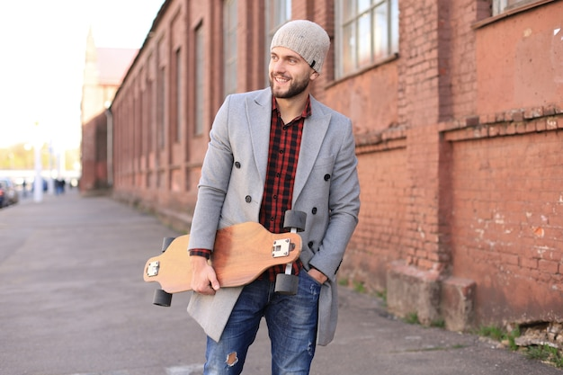 Knappe jonge man in grijze jas en hoed lopen op straat, met behulp van longboard.
