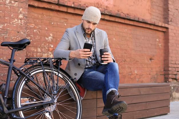 Knappe jonge man in grijze jas en hoed praten op de mobiele telefoon en glimlachen terwijl hij in de buurt van zijn fiets buiten zit.