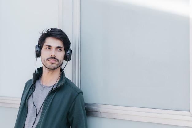 Knappe jonge man in oortelefoons buiten