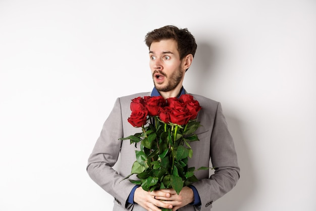 Knappe jonge man in pak met rode rozen, naar links kijkend met verbaasde en geschrokken uitdrukking, staande op valentijnsdag op witte achtergrond.