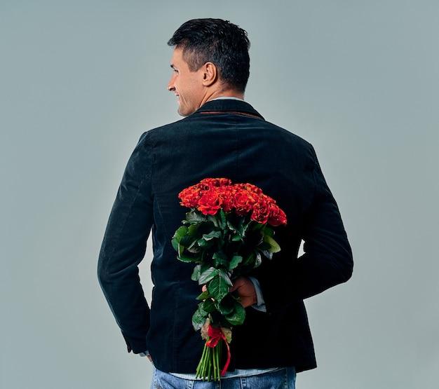 Knappe jonge man in pak staat met rode rozen achter de rug op grijs.