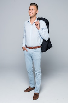 Knappe jonge man in shirt en spijkerbroek houdt zijn jas op de schouder geïsoleerd op lichtgrijze muur