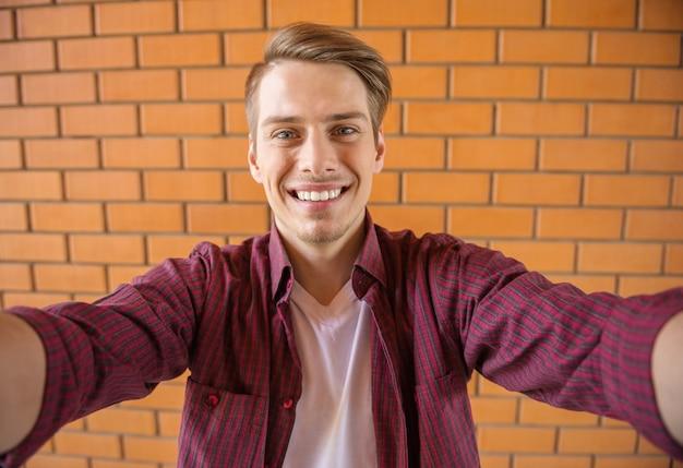 Knappe jonge man in slimme vrijetijdskleding selfie maken.