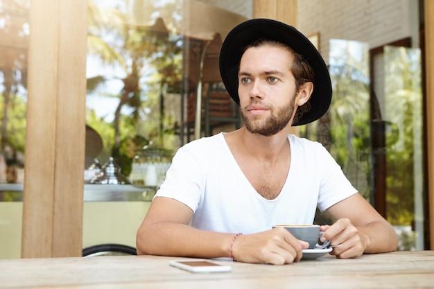 Knappe jonge man in stijlvolle zwarte hoed zitten aan tafel met mobiele telefoon en mok