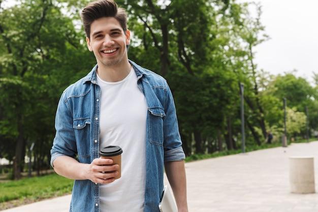 Knappe jonge man in vrijetijdskleding die afhaalkoffie drinkt en laptop vasthoudt terwijl hij door groen park loopt
