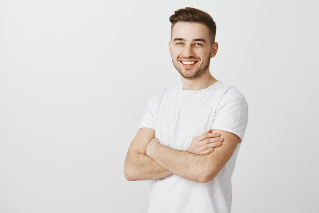 Knappe jonge man in wit t-shirt, kruis armen borst en glimlachend tevreden