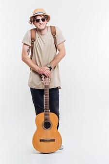 Knappe jonge man in zonnebril houden op de gitaar geïsoleerd op een witte achtergrond
