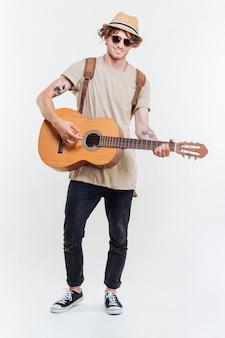 Knappe jonge man in zonnebril spelen op de gitaar geïsoleerd op een witte achtergrond