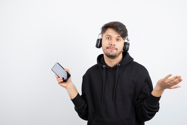 Knappe jonge man in zwarte hoodie met grote draadloze muziek koptelefoon