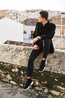 Knappe jonge man in zwarte poseren op straat