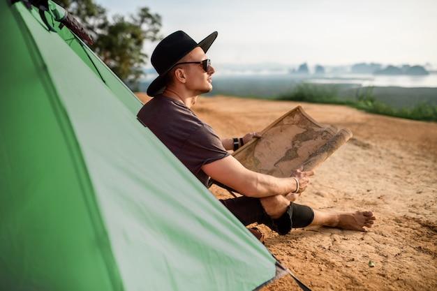 Knappe jonge man kijkend naar papieren kaart buitenshuis en zitten in de buurt van zijn groene tent. reizen, vakantie en vrijheid