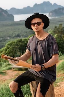 Knappe jonge man kijkend naar papieren kaart buitenshuis. terloops geklede man met kaart. prachtig uitzicht natuur. jonge reiziger die van zonnige dag geniet. reizen, vakantie en vrijheid