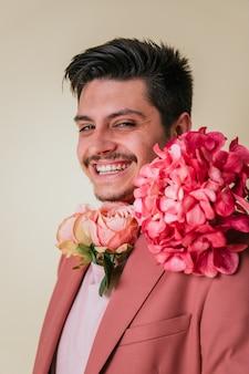 Knappe jonge man kijkt en glimlacht met bloemen om zijn nek, gekleed in een roze pak