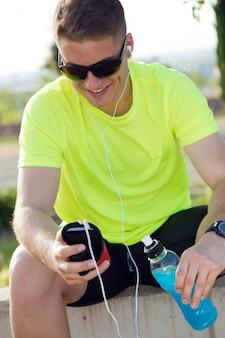 Knappe jonge man luisteren naar muziek na het rennen.