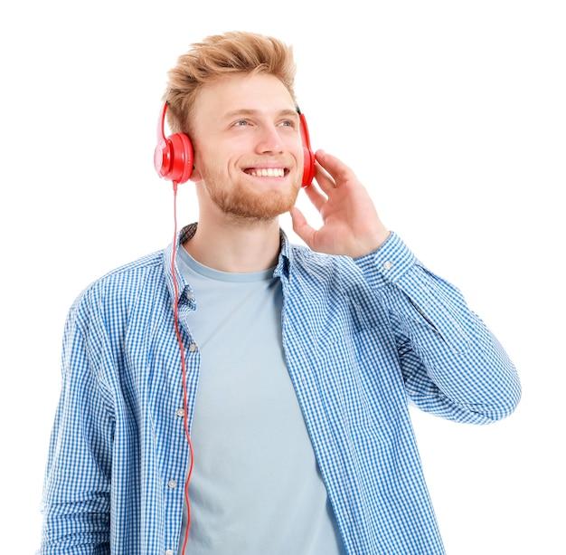 Knappe jonge man luisteren naar muziek op witte achtergrond