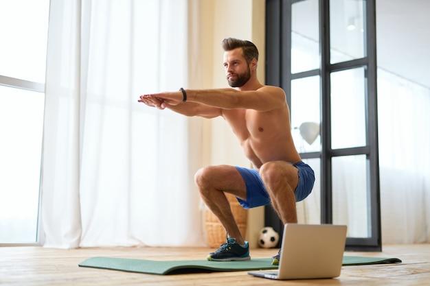 Knappe jonge man met atletisch lichaam die thuis squats doet