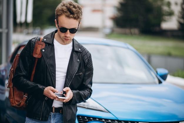 Knappe jonge man met behulp van de telefoon door de auto