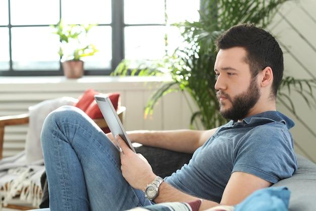 Knappe jonge man met behulp van digitale tablet of ebook