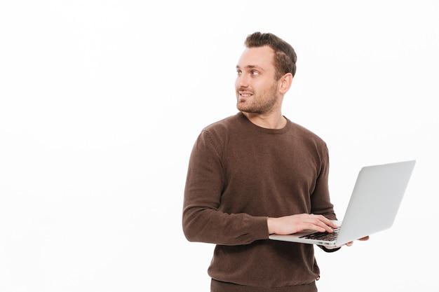 Knappe jonge man met behulp van laptopcomputer.