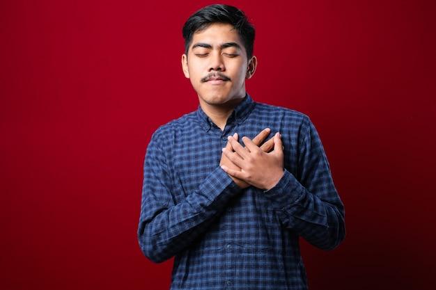 Knappe jonge man met casual kleding glimlachend met handen op borst met gesloten ogen en dankbaar gebaar op gezicht over rode achtergrond. gezondheidsconcept.