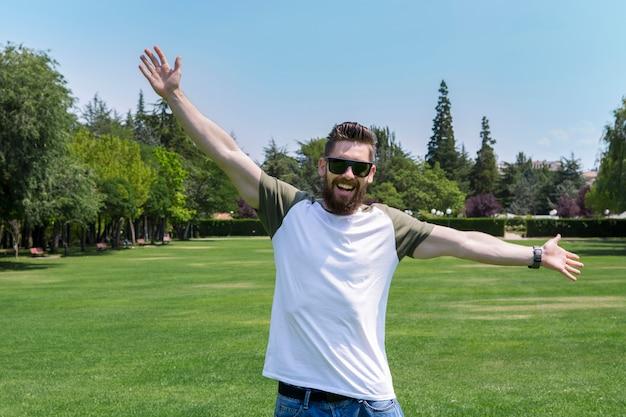 Knappe jonge man met een baard en zonnebril, genieten van de natuur, met een groen en lente landschap.