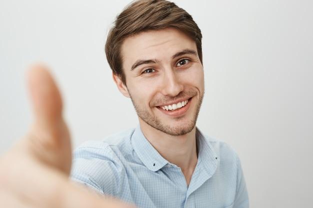 Knappe jonge man met een gelukkige glimlach, hand vooruit strekken