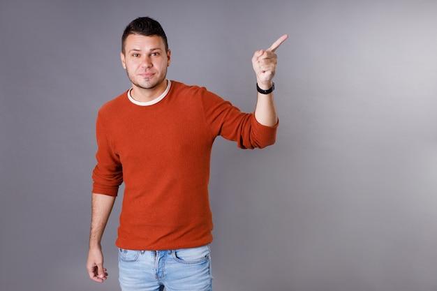 Knappe jonge man met een oranje trui die omhoog wijst