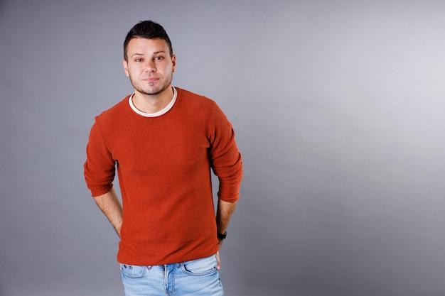 Knappe jonge man met een oranje trui