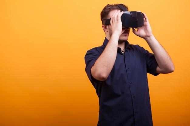 Knappe jonge man met een virtual reality-bril over gele achtergrond. nieuwe manier van amusement