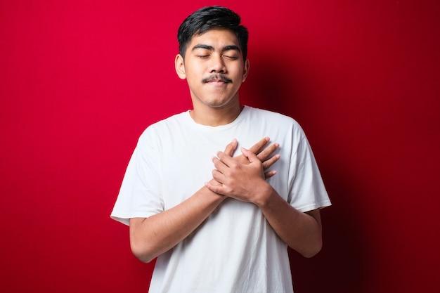 Knappe jonge man met een wit t-shirt glimlachend met handen op de borst met gesloten ogen en dankbaar gebaar op het gezicht over rode achtergrond. gezondheidsconcept.