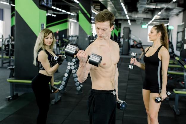 Knappe jonge man met gespierde naakte torso staande in de sportschool en traint biceps met halters samen met twee mooie jonge vrouwen op de achtergrond