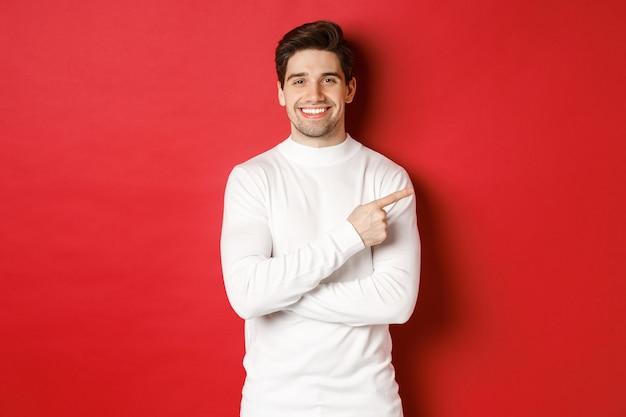 Knappe jonge man met haren in een witte trui die met de vingers naar de rechterbovenhoek wijst en glimlacht...