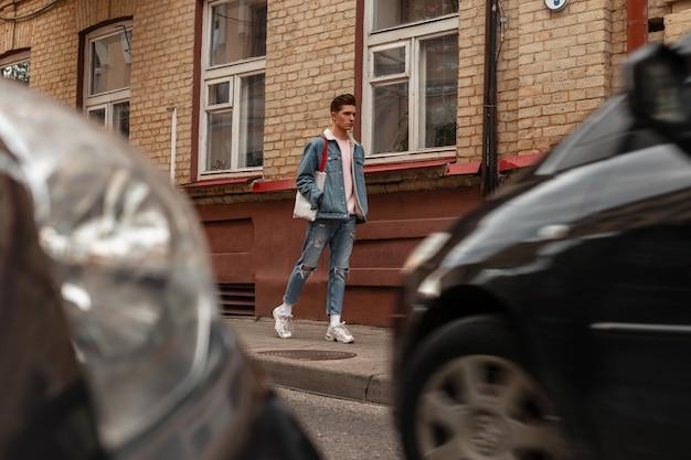 Knappe jonge man met kapsel in trendy blauwe casual denim kleding in witte trendy sneakers met vintage stoffen tas loopt op straat in de buurt van bakstenen gebouw en moderne auto's. aantrekkelijke man op wandeling.