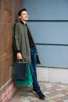 Knappe jonge man met kleurrijke boodschappentassen leunend op muur wegkijken