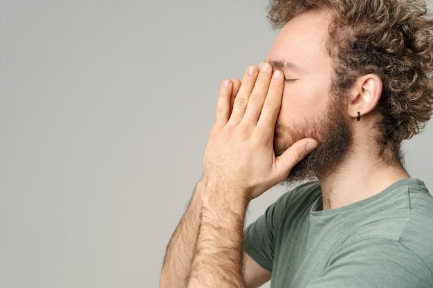 Knappe jonge man met krullend haar in olijf t-shirt geïsoleerd op een witte muur