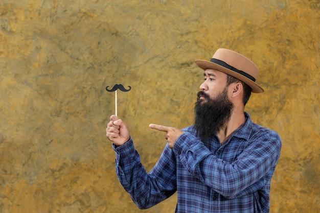 Knappe jonge man met lange baard met een speelgoed snor