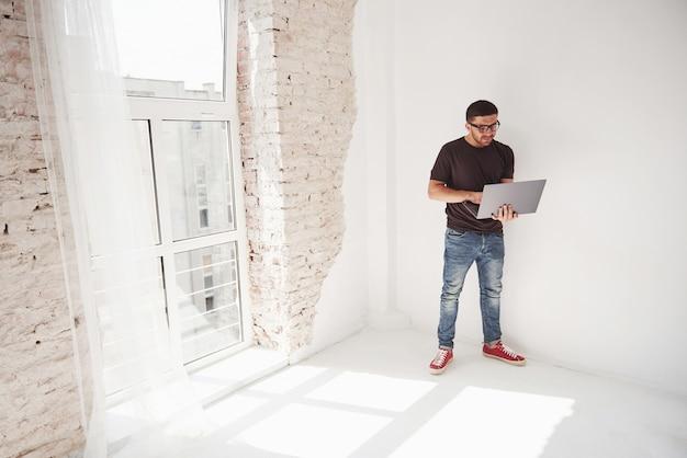 Knappe jonge man met laptop en controleer zijn tijdschema op witte achtergrond.