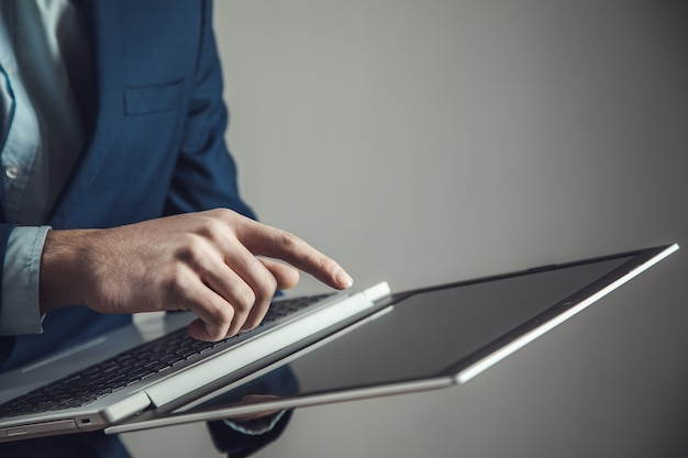 Knappe jonge man met laptop op donkere achtergrond