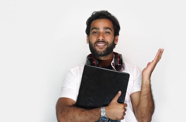 Knappe jonge man met laptop op witte achtergrond