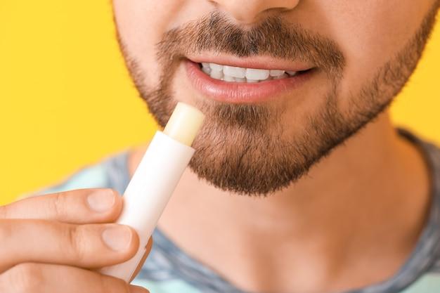 Knappe jonge man met lippenbalsem op kleur oppervlak, close-up