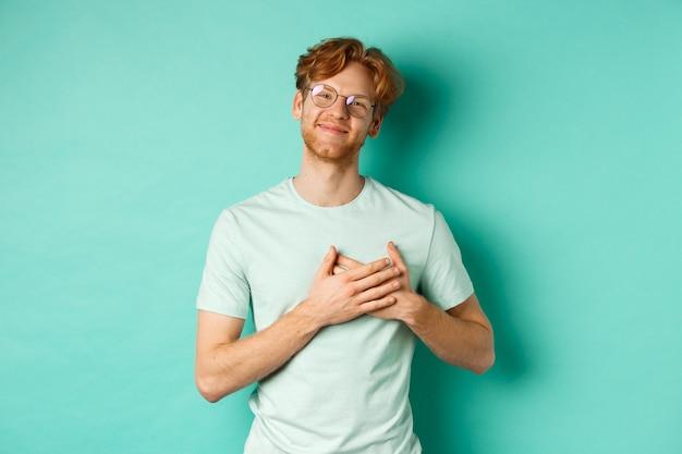 Knappe jonge man met rood haar en bril, hand in hand op het hart en glimlachend, dankjewel, dankbaar en ontroerd, staande over turkooizen achtergrond.