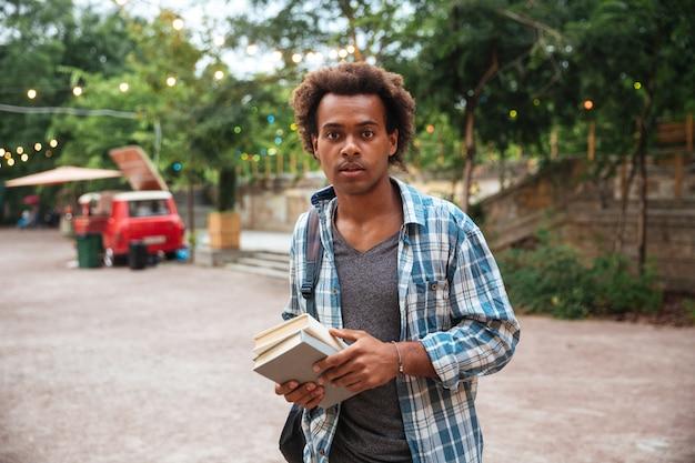 Knappe jonge man met rugzak en boeken staan in het park