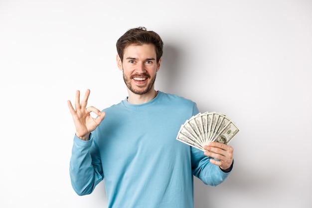 Knappe jonge man met snelle leningen geld, ok gebaar maken en lachend met contant geld, staande op een witte achtergrond.