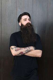 Knappe jonge man met staande voor houten zwarte muur met gekruiste armen