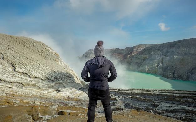 Knappe jonge man met uitzicht op de bergen hoog