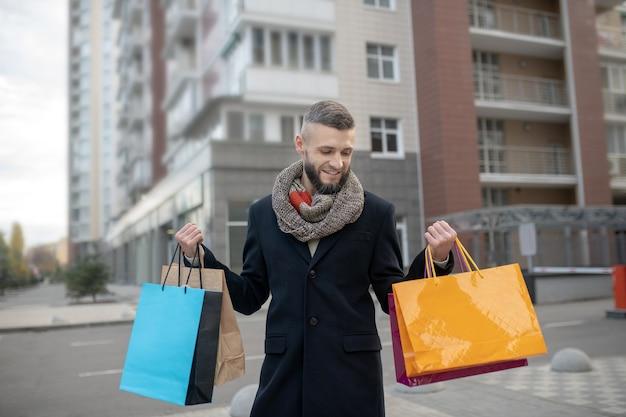 Knappe jonge man met veel boodschappentassen terwijl hij op straat stond