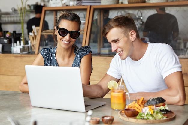 Knappe jonge man met wit t-shirt met iets op laptop pc aan zijn aantrekkelijke vrouwelijke metgezel in stijlvolle zonnebril tijdens de lunch in het café