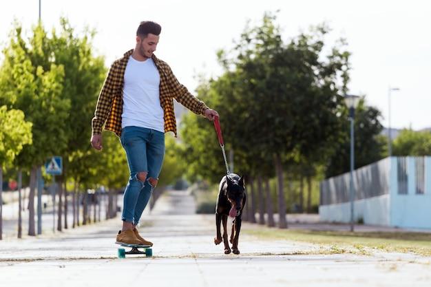 Knappe jonge man met zijn hond skateboarden in het park.